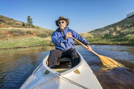 horsetooth reservoir: senior paddler in a decked expedition canoe on Horsetooth Reservoir, Fort Collins, Colorado, springtime scenery