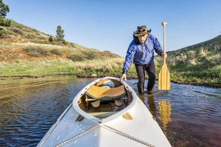 paddler: senior paddler and decked expedition canoe on the shore of Horsetooth Reservoir, Fort Collins, Colorado, springtime scenery Stock Photo