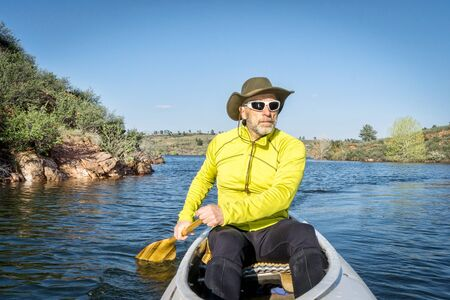 horsetooth reservoir: senior male paddling a decked expedition canoe on Horsetooth Reservoir, Fort Collins, Colorado, springtime scenery