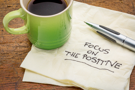 focus on the positive - motivational words handwritten on a napkin with a cup of espresso coffee Фото со стока