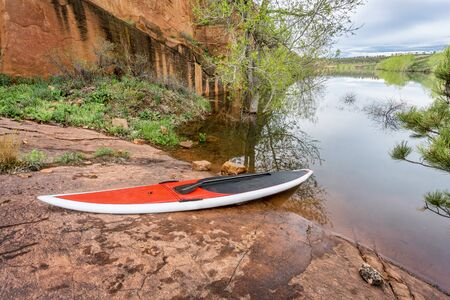 collins: red stand up paddleboard  with a paddle on rocky lake shore - Horsetooth Reservoir, Fort Collins, Colorado