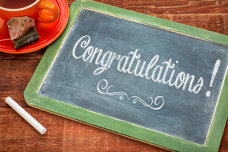 Congratulations! Text on a slate blackboard with chalk and cup of tea