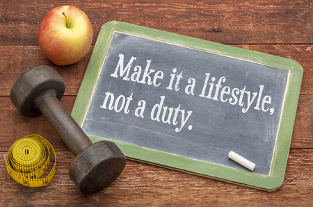 Maak er een levensstijl, geen plicht - fitness en gezond leven concept - leibord teken tegen verweerde rood geschilderde schuur hout met een halter, appel en meetlint Stockfoto