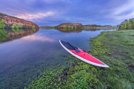 horsetooth reservoir: dusk over calm lake with a red stand up paddleboard  with a paddle on shore - Horsetooth Reservoir, Fort Collins, Colorado