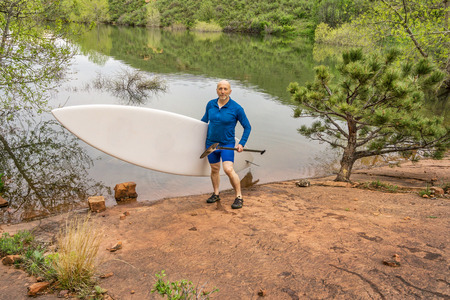 horsetooth reservoir: senior paddler carrying paddleboard and paddle on a rocky shore of a lake - Horsetooth Reservoir, Fort Collins, Colorado