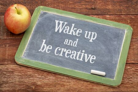 creativity: Wake up and be creative  - inspirational positive words on a slate blackboard against red barn wood