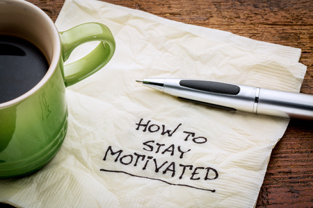 How to stay motivated - handwriting on a napkin with a cup of espresso coffee Standard-Bild