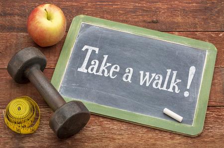 dar un paseo - concepto de fitness - pizarra signo pizarra contra la madera resistida del granero rojo pintado con una pesa de gimnasia, manzana y cinta métrica
