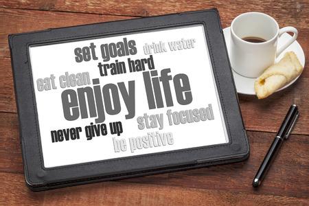コーヒーのカップとデジタル タブレットの健康的なライフ スタイルの単語の雲人生を楽しむ