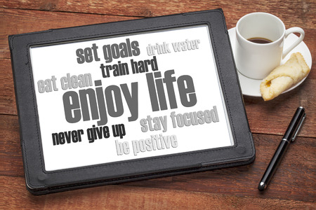 vida sana: disfrutar de la vida - estilo de vida saludable nube de palabras en una tableta digital con una taza de café