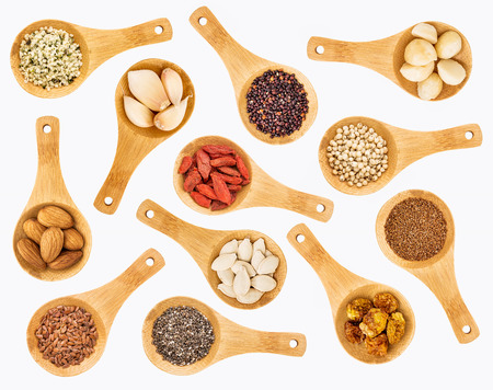 superfruit: superfood grain, seed, berry, nuts and garlic abstract - top view of  random isolated on white wooden spoons