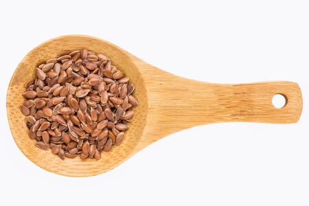 organic flax seed: brown flax seeds on a small wooden spoon isolated on white with a clipping path Stock Photo