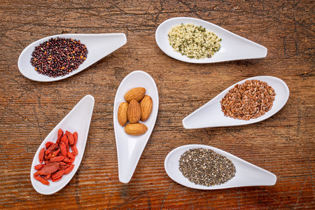 abstract seed: superfood grain, seed, berry, and nuts  abstract - top view of spoon bowls against rustic wood