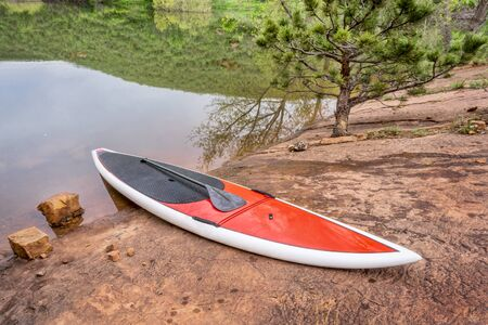 horsetooth reservoir: red stand up paddleboard  with a paddle on rocky lake shore - old sandstone quarry at Horsetooth Reservoir, Fort Collins, Colorado