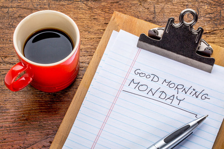 good: Good morning, Monday - handwriting on a small clipboard with a cup of coffee