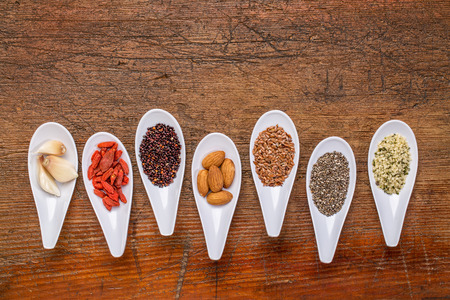 hemp hemp seed: superfood grain, seed, berry, nuts and garlic cloves abstract - top view of spoon bowls against rustic wood with a copy space Stock Photo