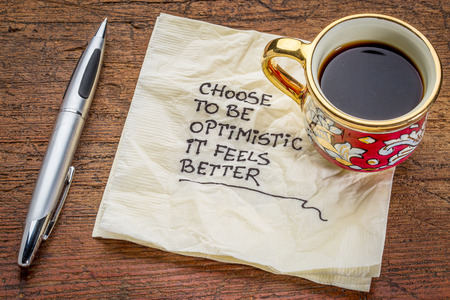 choose to be optimistic, it feels better - motivational handwriting on a  napkin with a cup of coffee 免版税图像