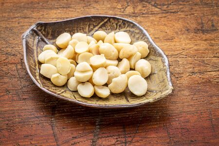 nuts: macadamia nuts on a ceramic leafs shaped bowl against rustic wood Stock Photo