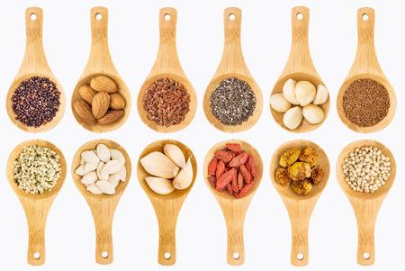 ajo: grano súper alimento, semillas, bayas, nueces y ajo abstracta - vista superior aislado en cucharas de madera blancos (dos filas) Foto de archivo