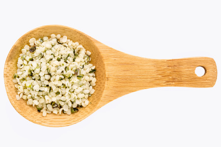 hemp hemp seed: hemp seed hearts on a small wooden spoon isolated on white with a clipping path Stock Photo