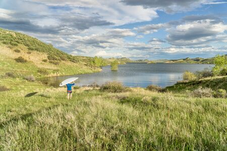 horsetooth reservoir: male paddler is carrying hi SUP paddleboard to a lake - Horsetooth Reservoir near Fort Collins, Colorado, at springtime