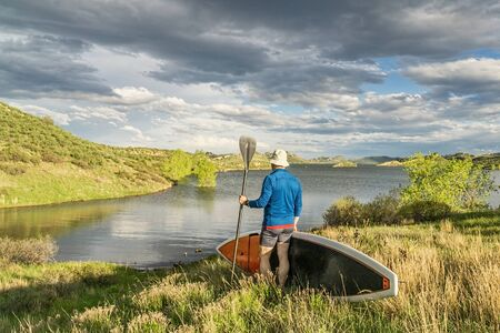 collins: male paddler with stand up paddleboard (SUP) on a grassy shore of mountain lake - Horsetooth Reservoir near Fort Collins, Colorado