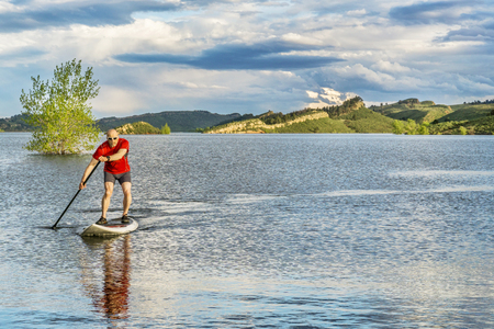 horsetooth reservoir: mountain lake landscape with a senior male paddling a SUP paddleboard with a copy space - Horsetooth Reservoir, Fort Collins, Colorado