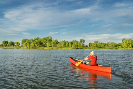 collins: male paddler paddling a red canoe on a local lake in Fort Collins, Colorado