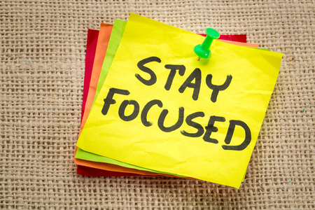 focus on: stay focused reminder on a sticky note - motivation concept