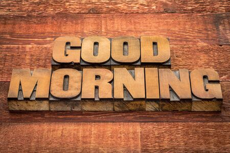 wood type: good morning typography - text in vintage letterpress wood type against rustic barn wood table Stock Photo