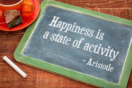 cotizacion: La felicidad es un estado de actividad, una cita de Aristóteles - palabras de motivación en una pizarra pizarra con tiza y una taza de té Foto de archivo