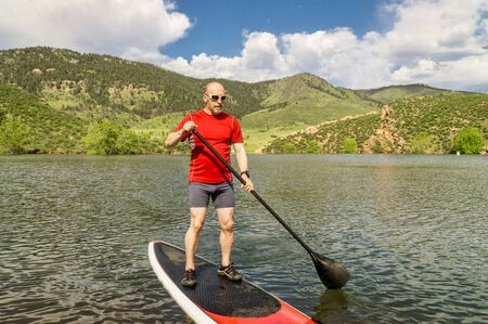 horsetooth reservoir: male paddler enjoying stand up paddling on a sunny summer day - Horsetooth Reservoir, Fort Collins, Colorado