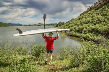 paddler: male paddler carrying a stand up paddleboard and a paddle on a sunny summer day - Horsetooth Reservoir, Fort Collins, Colorado