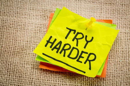 harder: try harder - motivation words on a  yellow sticky note against burlap canvas Stock Photo