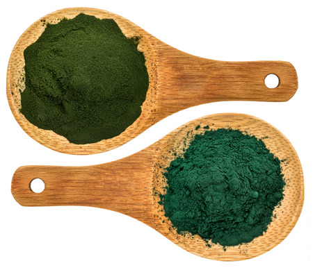 chlorella ans spirulina supplemt powder - top view of isolated wooden spoons Foto de archivo