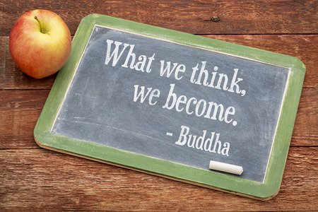What we think we become - Buddha quote  on a slate blackboard against red barn wood