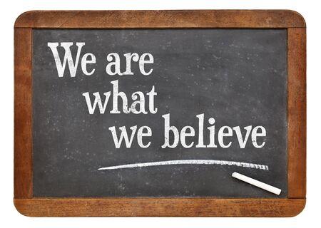 believe: Somos lo que creemos - texto en una pizarra pizarra de la vendimia Foto de archivo