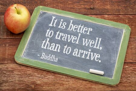 spiritual journey: It is better to travel well than arrive  - Buddha quote  on a slate blackboard against red barn wood Stock Photo