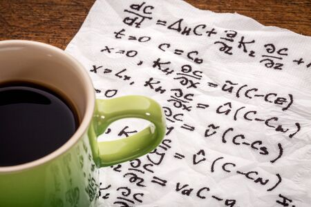 derivation: mathematical equations of physics - handwriting on a napkin with a cup of coffee Stock Photo