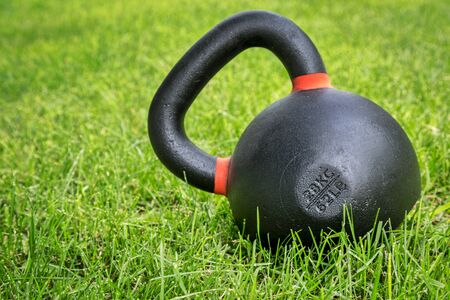 outdoor fitness: heavy iron competition kettlebell (62lb - 28 kg) on green grass in backyard - outdoor fitness concept