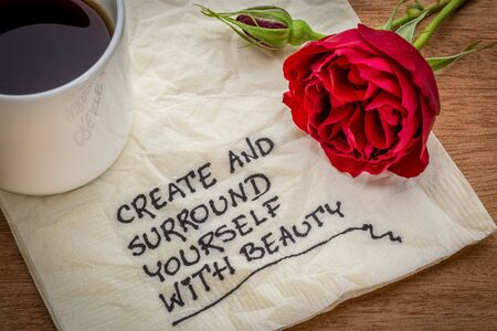 create and surround yourself with beauty - inspirational handwriting on a napkin with a cup of coffee and red rose