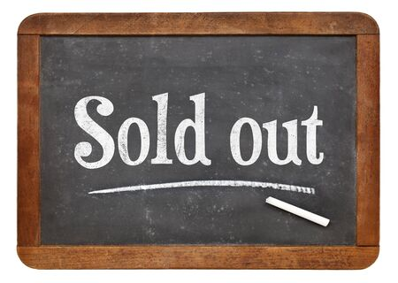 white chalk: Sold out sign  - white chalk text on an isolated  vintage slate blackboard Stock Photo