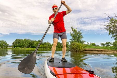 fort collins: senior muscular male paddler enjoying paddling stand up paddleboard  on a local lake in Fort Collins, Colorado