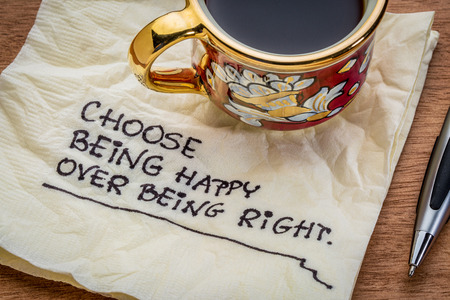 Choose being happy over being right - inspirational advice - handwriting on a napkin with cup of coffee