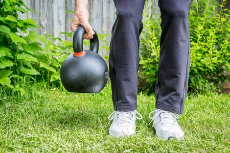 outdoor fitness: fitness workout with a heavy iron competition kettlebell (62lb28 kg) on green grass in backyard - outdoor fitness concept