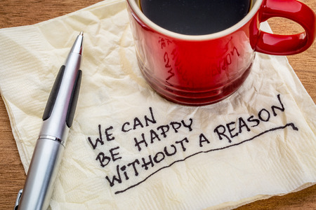 spiritual: We can be happy without reason - inspirational words - handwriting on a napkin with cup of coffee