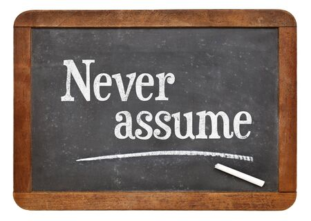 white chalk: Never assume advice  - text in white chalk on a vintage slate blackboard