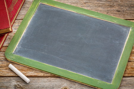 blank slate: blank slate blackboard with a white chalk and a stack of books against rustic wooden table