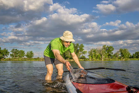 fort collins: male paddler is washing his SUP paddleboard before starting workout on a local lake in Colorado Stock Photo