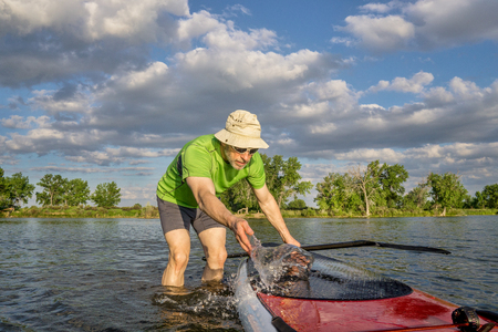 paddler: male paddler is washing his SUP paddleboard before starting workout on a local lake in Colorado Stock Photo